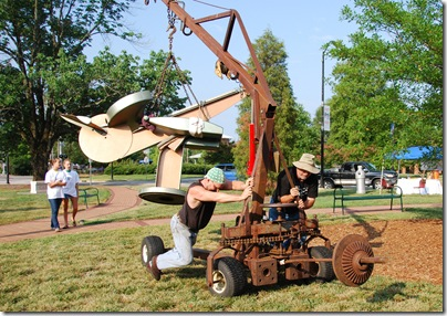 "Mike Roig and fellow sculptor Wayne Vaughn move ""Air Guitar"" into place -photo by Kim Marchesseault"