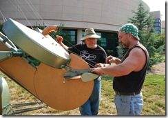 "Fellow sculptor Wayne Vaughn assists Mike Roig in stringing  ""Air Guitar"""